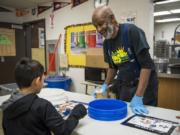 Greg Davis, day custodian, helps students organize their lunch plates for the cafeteria composting system at Martin Luther King Elementary School in Vancouver. Davis has worked for the school district since 1986 and at Martin Luther King Elementary School for 25 years. He has plans to retire shortly after the school makes a big move to a new building by September 2020.