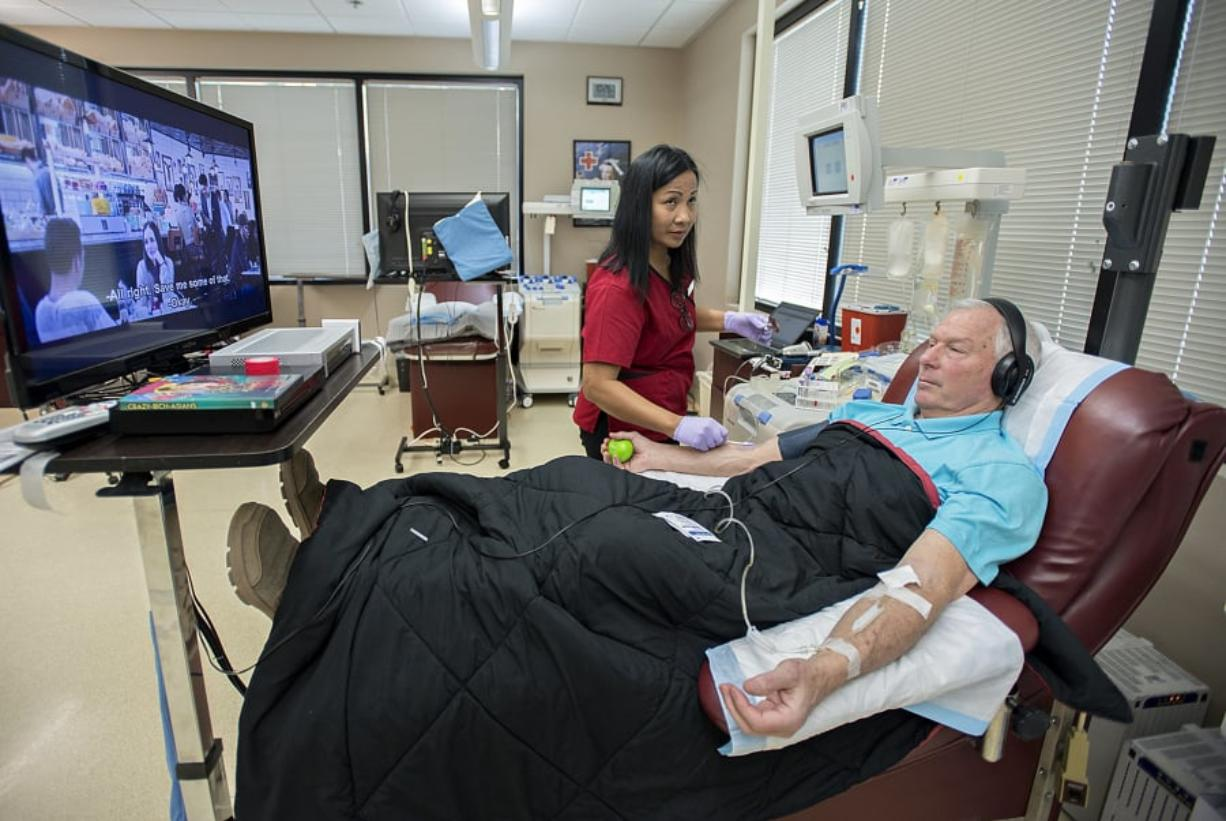 """Phlebotomist Sotheary Chet, center, works with platelet donor John Reinhardt of Battle Ground at the American Red Cross Blood Donor Center in Vancouver. Reinhardt, a regular platelet donor, decided to watch """"Crazy Rich Asians"""" over the two-hour donation process. Platelets, which have a shelf life of five days, are mainly used for trauma injuries."""
