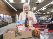 """Christina Brown of Vancouver fills a box with groceries while checking out at the Vancouver Grocery Outlet. The store eliminated single-use plastic bags on March 1 and now offers boxes for customers who did not bring reusable bags. """"I'm pretty glad,"""" Brown said."""