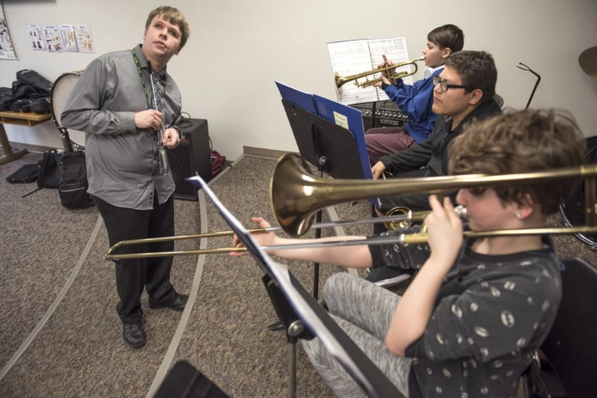 Music teacher Shane Dittmar of the Washington State School for the Blind, left, listens carefully as beginning band students Jaymes Gummere (in back), Xavier Lopez and Olivia McGraw work on scales and rhythms. Nathan Howard/The Columbian