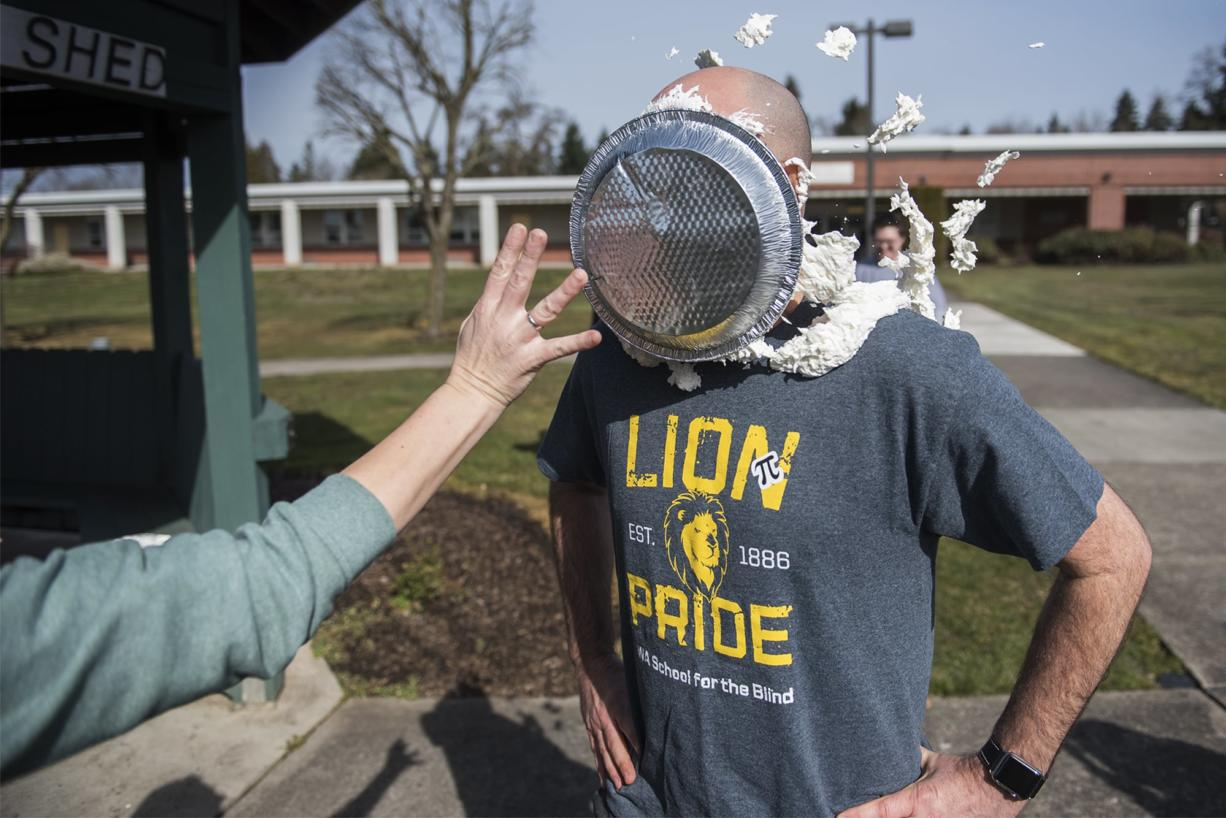 Scott McCallum, superintendent of the Washington State School for the Blind, takes a pie to the face as a reward for students who memorized 50 digits of Pi at the Washington State School for the Blind on Thursday afternoon, March 14, 2019.