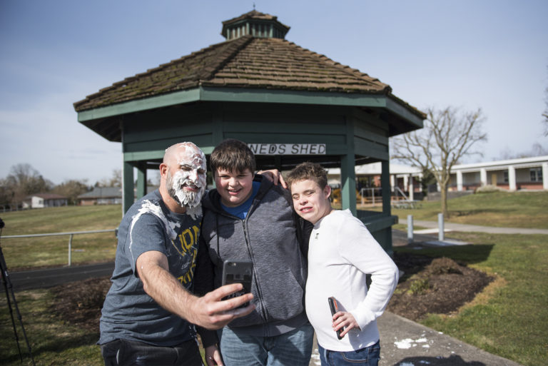 Scott McCallum, superintendent of the Washington State School for the Blind, from left, poses for a selfie with Freshman Deegan Richardson and Eighth Grader Fenix Roarke after McCallum took a pie to the face as a reward for students who memorized 50 digits of Pi at the Washington State School for the Blind on Thursday afternoon, March 14, 2019.