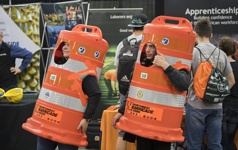 Christina Riley of Laborers' International Union of North America, left, and Joey Schiro, 19, of Legacy High School greet fellow job fair participants while dressed as construction barricades at the Clark County Events Center on Tuesday morning, March 19, 2019. (Amanda Cowan/The Columbian)