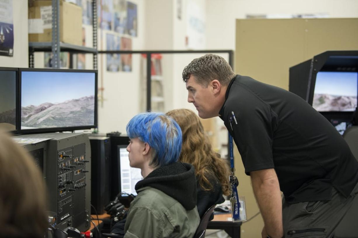 Junior Seth Trimbo, 16, takes a seat behind the wheel of a flight simulator as aviation technology instructor Robert Reinebach offers assistance. The Cascadia Tech Academy aviation program has 92 students enrolled from 10 Clark County school districts.