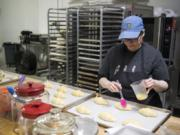 Deda's Bakery co-owner Catherine Misener prepares croissants for baking. If she had to do over again, she says a $10,000 espresso machine would have been a good investment for the bakery.