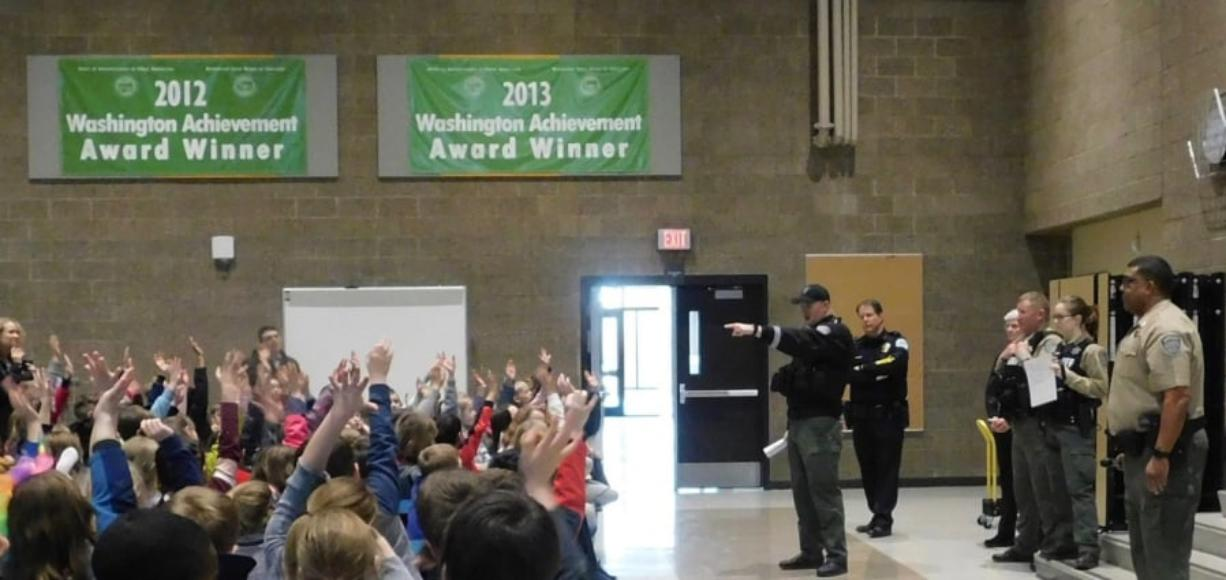 Ridgefield: An officer from the Clark County Sheriff's Department answers questions during a visit to South Ridge Elementary School as part of the Police Activities League.