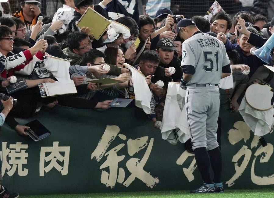 21a58b7db65 Seattle Mariners right fielder Ichiro Suzuki gives his autograph to fans  prior to a pre-