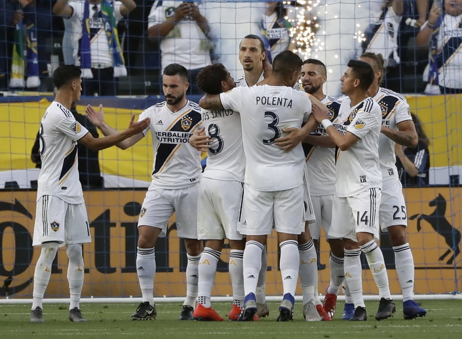c955014eea9 Los Angeles Galaxy forward Zlatan Ibrahimovic, center, is hugged by  teammates after scoring against