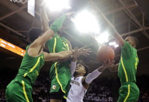 Washington guard David Crisp, second from right, is blocked by Oregon forward Kenny Wooten, second f