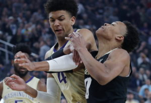 Washington's Matisse Thybulle, left, fouls Colorado's Shane Gatling during the first half of an NCAA