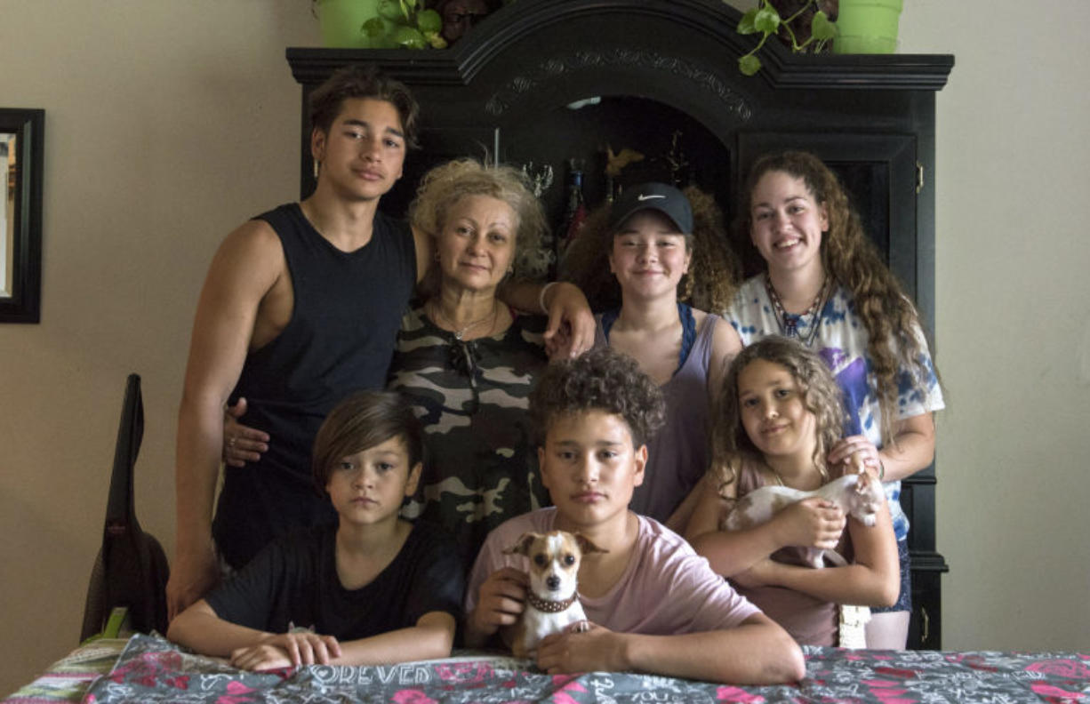 The Flores family sits for a portrait at their dining room table in Vancouver on Aug. 23, 2017. Since Ramon Flores-Garcia was deported in August 2017 to Mexico, after staying at a Motel 6 in Everett, his family has become homeless and moved to Chula Vista, Calif., to be closer to him.