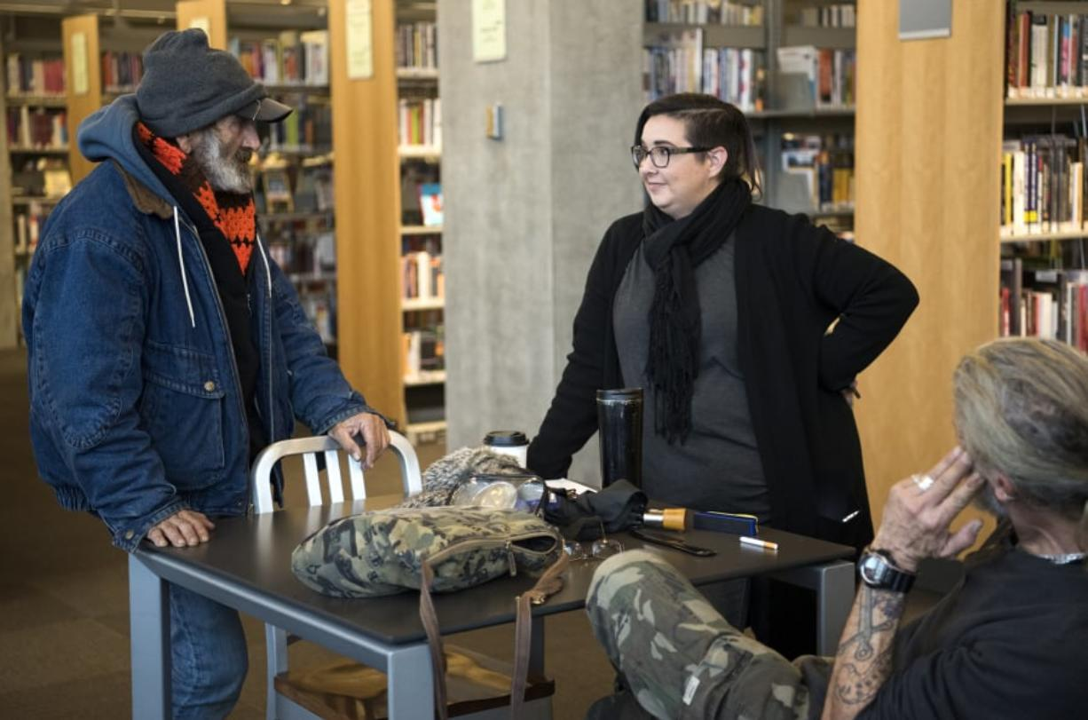 Jack Crowley, left, chats with Jamie Spinelli, a case worker with Community Services Northwest, on Dec. 11 in the Vancouver Community Library. Crowley had been homeless for about 34 years but recently got housing. As part of a pilot project, Spinelli works in the library to help connect homeless people with resources.