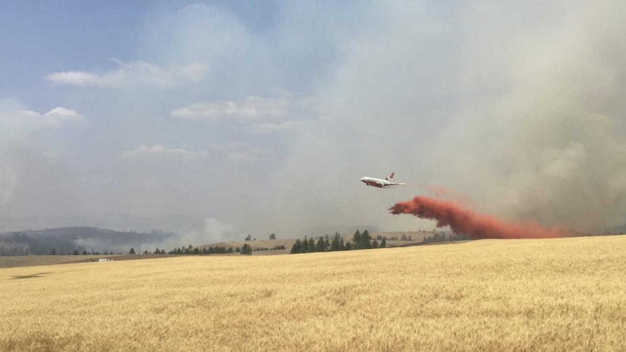 An air tanker drops retardant on a wheat field as crews battled an Eastern Washington wildfire last August.