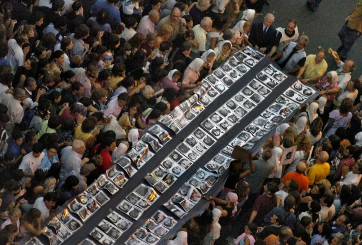 Demonstrators hold a big banner with pictures of the missing people during a march from the National Congress to Plaza de Mayo in Buenos Aires in March 2006 during the 30th anniversary of the coup which started the most bloody dictatorship (1976-1983) in Argentina.