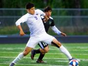 Coumbia River's Aaron Espinosa (9) plays the ball in front of Woodland's Anthony Clifford (12).