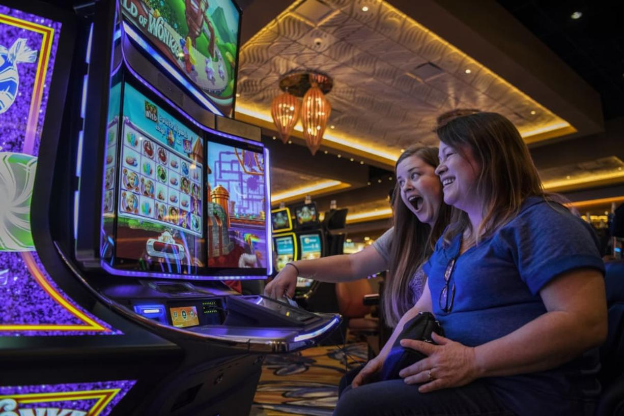 "Alisha Alexander, left, and her mother, Lisa Lugar, right, both of Ridgefield, play the new Willy Wonka World of Wonka slot machine at ilani. Lugar said she and her daughter have come to enjoy ""Forever Young Mondays,"" where guests 50 years and older receive special perks. Wednesday marks ilani's two-year anniversary."