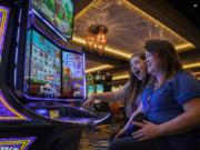 """Alisha Alexander, left, and her mother, Lisa Lugar, right, both of Ridgefield, play the new Willy Wonka World of Wonka slot machine at ilani. Lugar said she and her daughter have come to enjoy """"Forever Young Mondays,"""" where guests 50 years and older receive special perks. Wednesday marks ilani's two-year anniversary."""