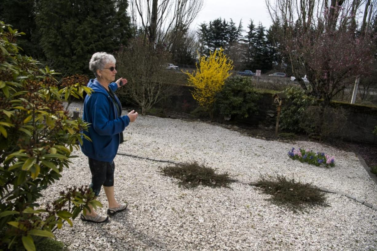 Jennifer Munson of Vancouver describes the proximity of her backyard to Highway 14, which is due to be widened. Munson and many of her neighbors along Southeast 35th Street believe the project should include extending a sound wall nearer to their homes.