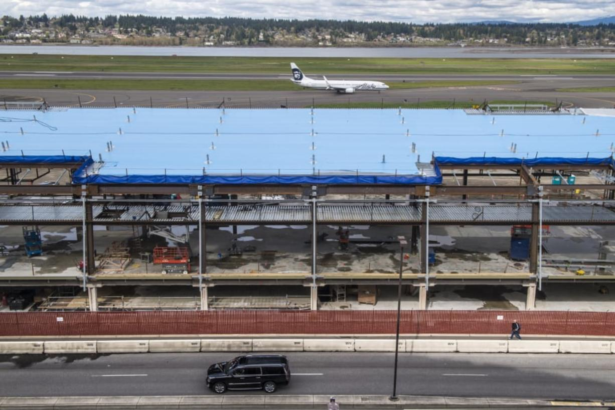 An Alaska Airlines jet taxis behind the Concourse E extension at Portland International Airport. The project, scheduled for completion in June 2020, is part of a $2 billion package of PDX improvements.