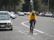 Cyclist Maurice Goudeau of Vancouver cruises past Clark College as he approaches the intersection of Fort Vancouver Way and McLoughlin Boulevard in the bike lane last week. At top, a sign near Clark College offers directions for people on two wheels as well as four.