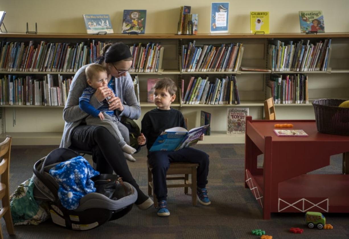 Katie Didyk of Battle Ground holds her son Benny, 9 months, and reads with her son Artem, 4, at the Battle Ground Community Library, which will close for three weeks starting Monday for upgrades, one of which is rearranging furniture to make the children's area more comfortable for families. While Battle Ground will have some minor upgrades, Fort Vancouver Regional Libraries is also in the process of trying to build four new buildings to increase services around the county.