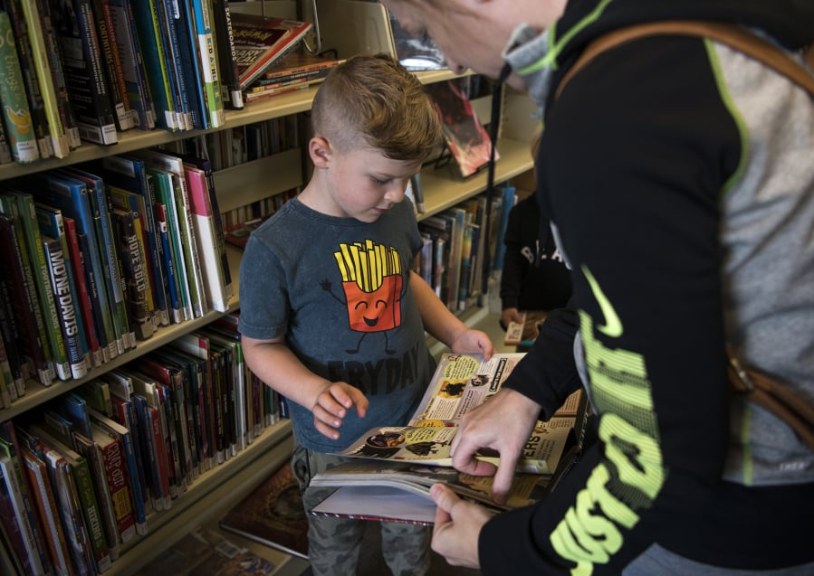 0d1f1463 Jude Siebert, 5, of Battle Ground picks out books with his mother, Jen