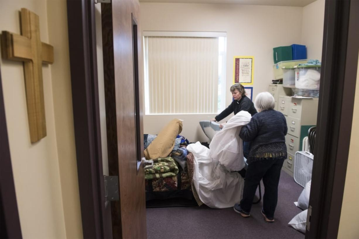 """Battle Ground Community United Methodist Church Pastor Susan Boegli, left, and Jean Brown prepare a bedroom for guests arriving Wednesday night. The church is taking a turn hosting Family Promise of Clark County, a new shelter that rotates to a different congregation each week. """"Sunday when people come to church this will all be put away,"""" Brown said."""