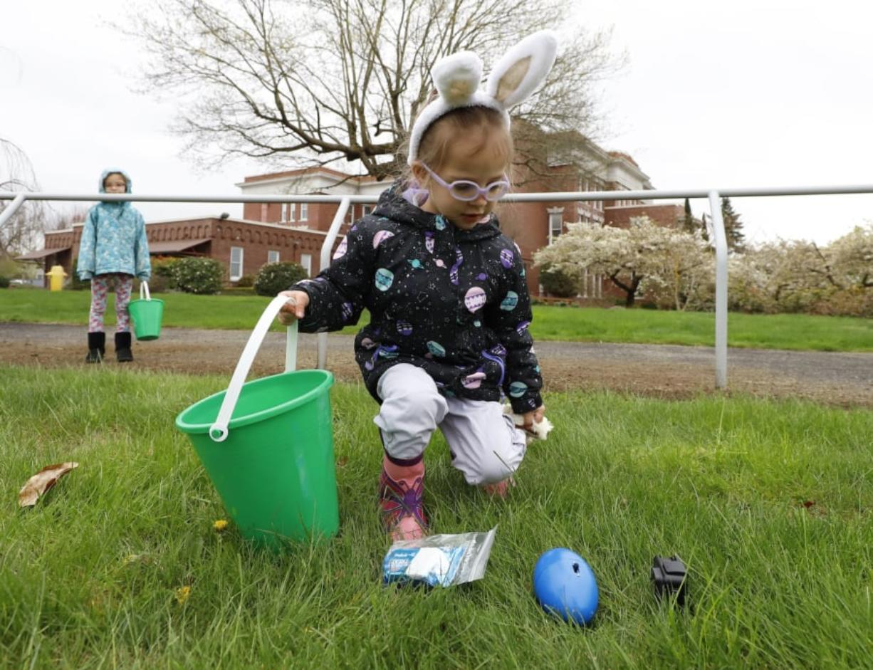Stella Childers, 3, of Vancouver stoops for a beeping egg during an Easter egg hunt for visually impaired children. Visually impaired kids, such as her younger brother, and their sighted siblings participated.