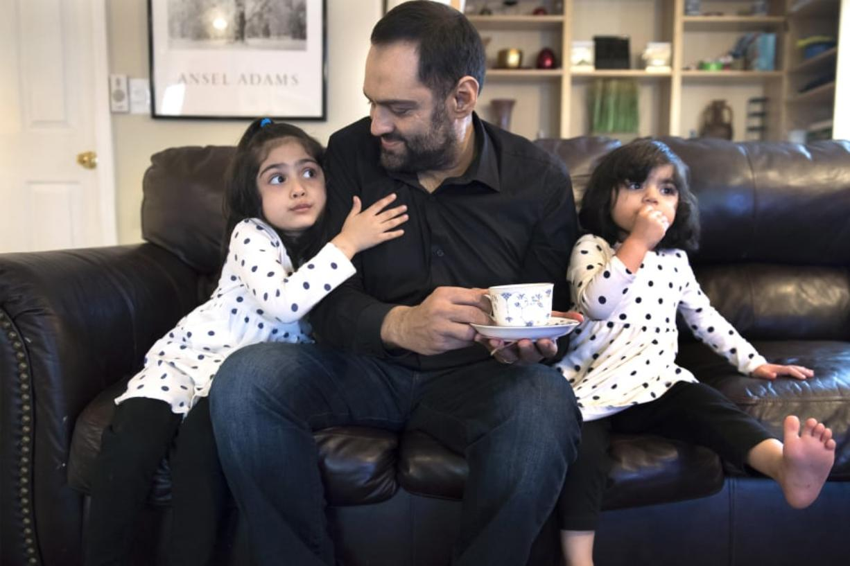 Sana Mir, 4, from left, tries to get another sip of her dad's tea, as Ahsan Mir, 50, and Asiya Mir, 2, watch a show after dinner at their Vancouver home. Ahsan was diagnosed with kidney failure about eight years ago, but he ignored his diagnosis until recently. Now he's trying to seek help through a kidney transplant. Nathan Howard/The Columbian