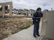 Ed Stanley of the U.S. Postal Service prepares a bank of mailboxes Wednesday at a new Clark County housing development, the Meadows at 58th Street in the Minnehaha area. Clark County's population growth cycle is continuing at a rate faster than the rest of the Portland metro area.