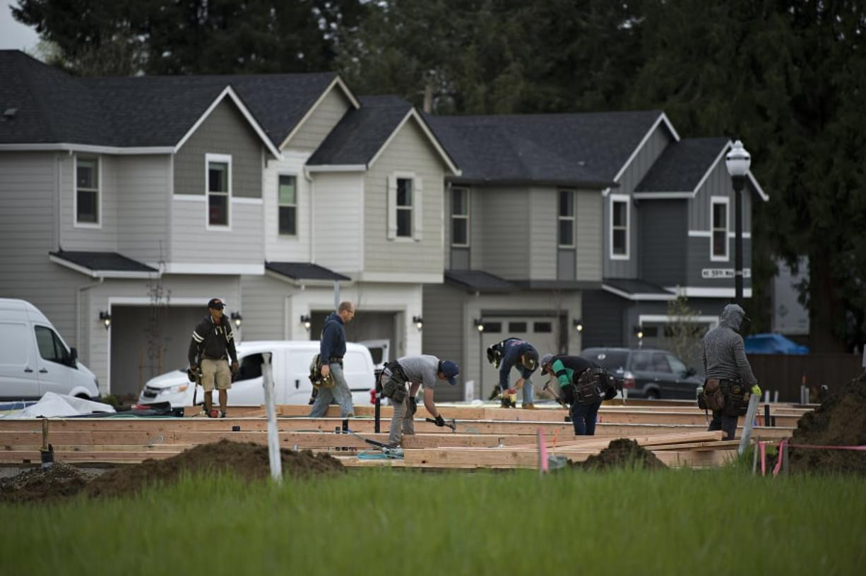 Homes at various stages of construction are seen at Meadows at 58th Street in the Minnehaha area as workers lend a hand to the project Wednesday morning. Amanda Cowan/The Columbian
