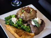 The top sirloin steak with a loaded baked potato and a side of broccoli and garlic bread at Billy Blues Bar and Grill.