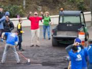 Colin Fogarty, executive director of Confluence, center, cheers on volunteers moving the last bits of a mulch pile.