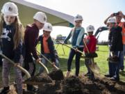 Students from Sifton Elementary School break ground Wednesday on the site of a future elementary school campus during a school assembly in Vancouver.