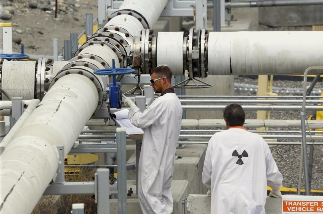 """Workers wearing protective clothing and footwear inspect a valve at the """"C"""" tank farm on the Hanford Nuclear Reservation near Richland in 2014."""