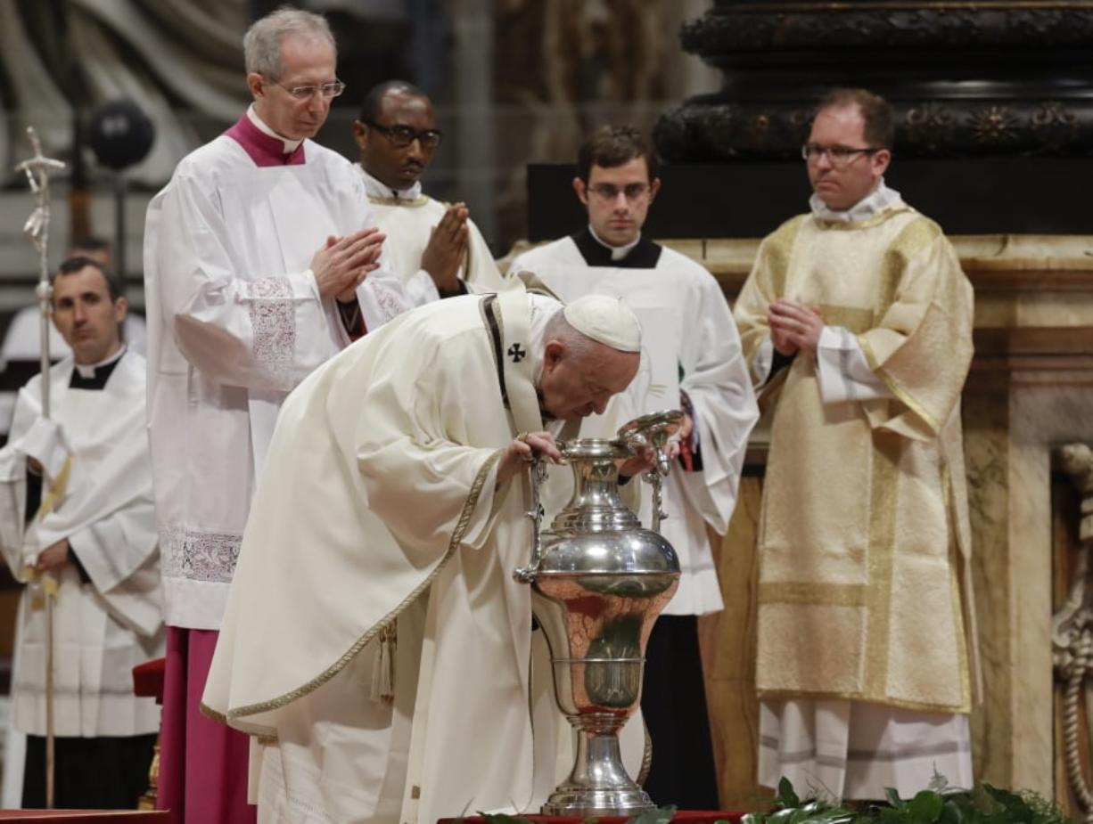 Pope Francis blows inside an amphora containing holy oil during a Chrism Mass inside St. Peter's Basilica on Thursday at the Vatican. During the Mass, the Pontiff blesses a token amount of oil that will be used to administer the sacraments for the year.