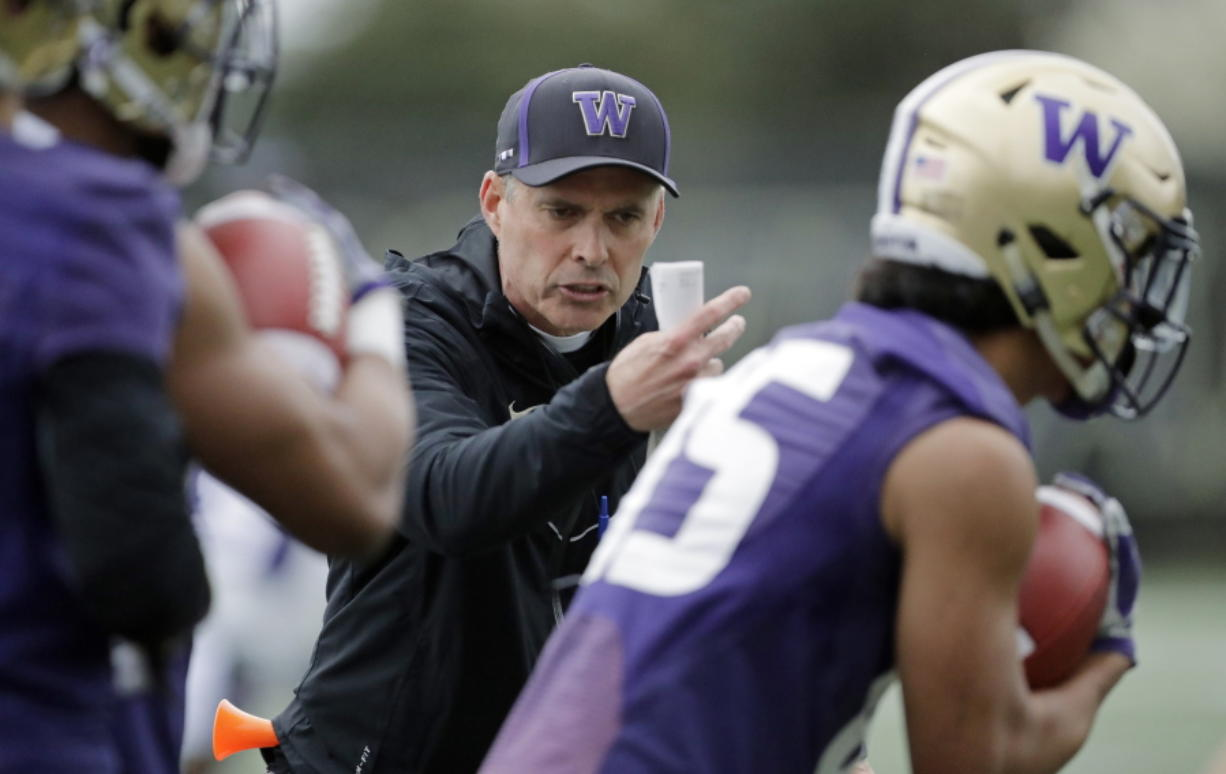 Washington head coach Chris Petersen talks to players as they run drill during the first day of spring NCAA college football practice, Wednesday, April 3, 2019, in Seattle. (AP Photo/Ted S.