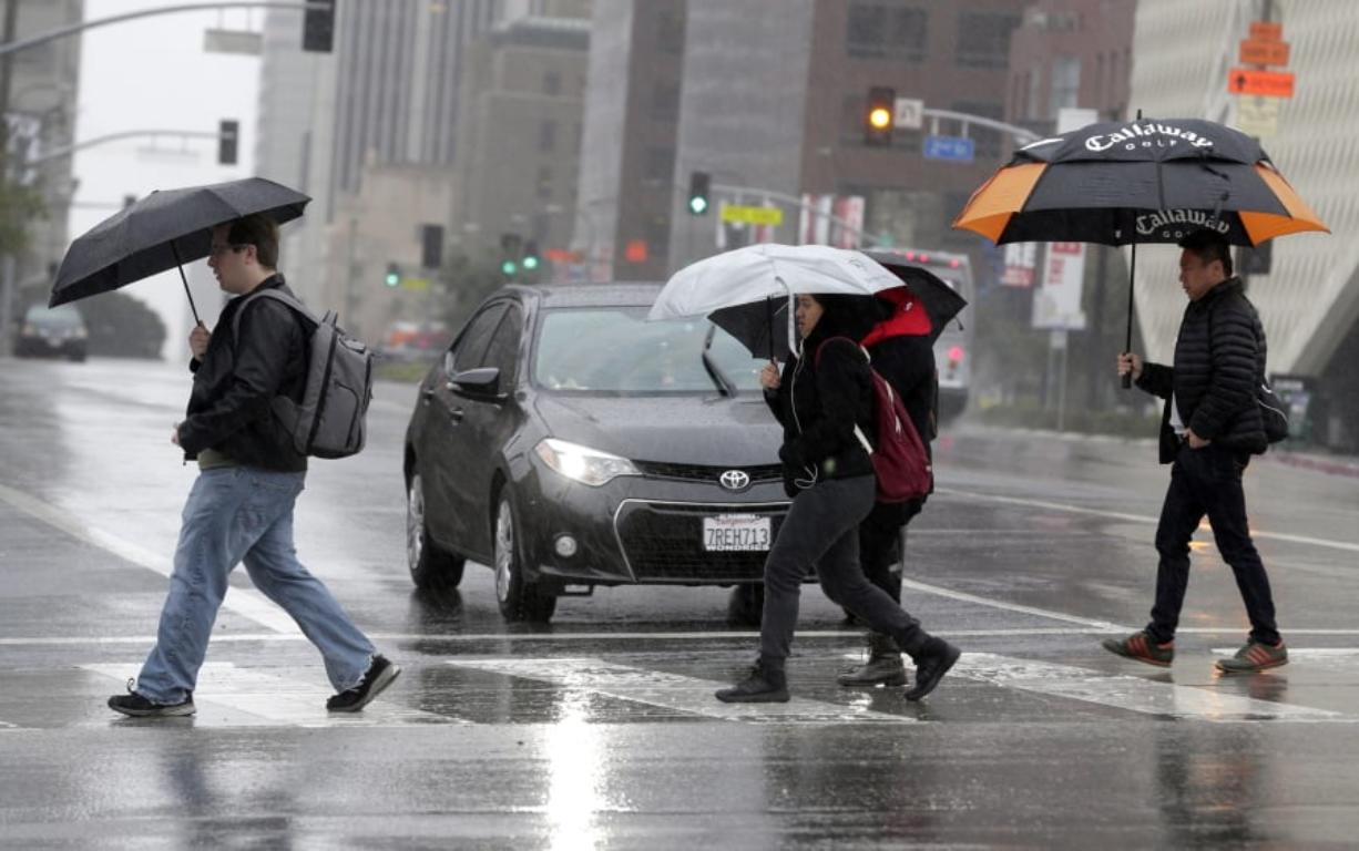 FILE - In this Monday, Feb. 6, 2017 file photo, pedestrians cross a rainy street in downtown Los Angeles. According to a study released in April 2019 in the Bulletin of the American Meteorological Society, even light rain significantly increases the risk of a fatal car crash.