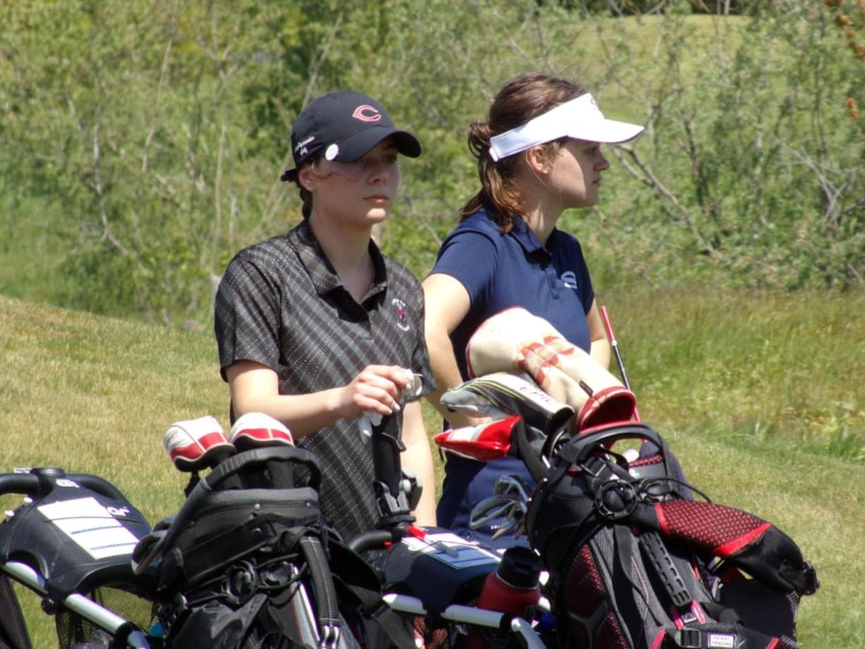 Camas' Emma Cox (left) stands with Skyview's Maddy Startwalt between shots at the 4A district girls golf tournament (Tim Martinez/The Columbian)