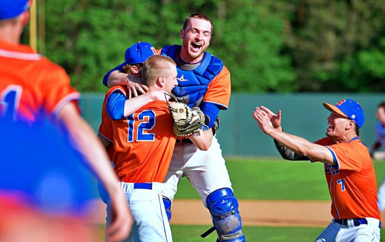 The members of the Ridgefield baseball team celebrate their 1-0 win over W.F. West on Wednesday, clinching a berth to the state tournament. Joshua Hart/The Columbian