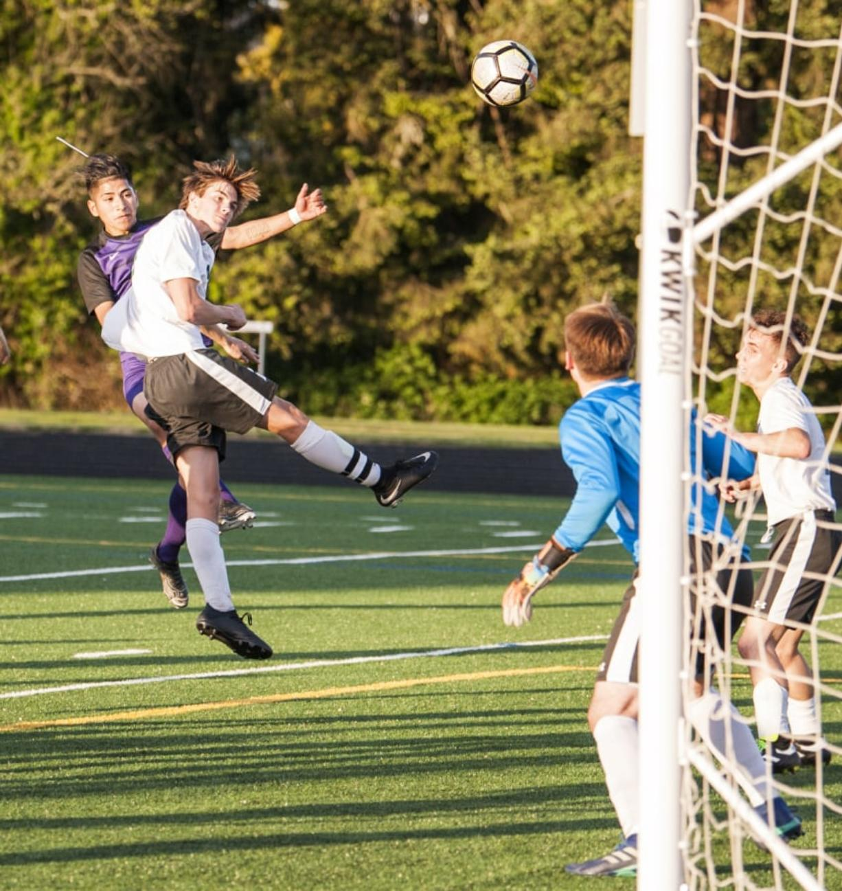 Columbia River's Julian Villa-Salas, left, admires his header over Woodland's Brooks Massey as the ball sails toward Woodland goalkeeper Treyson Thrall, who deflected it into the net. The goal put the Chieftains up 1-0 on the way to 3-0 victory Thursday at Chieftain Stadium in the 2A district championship.