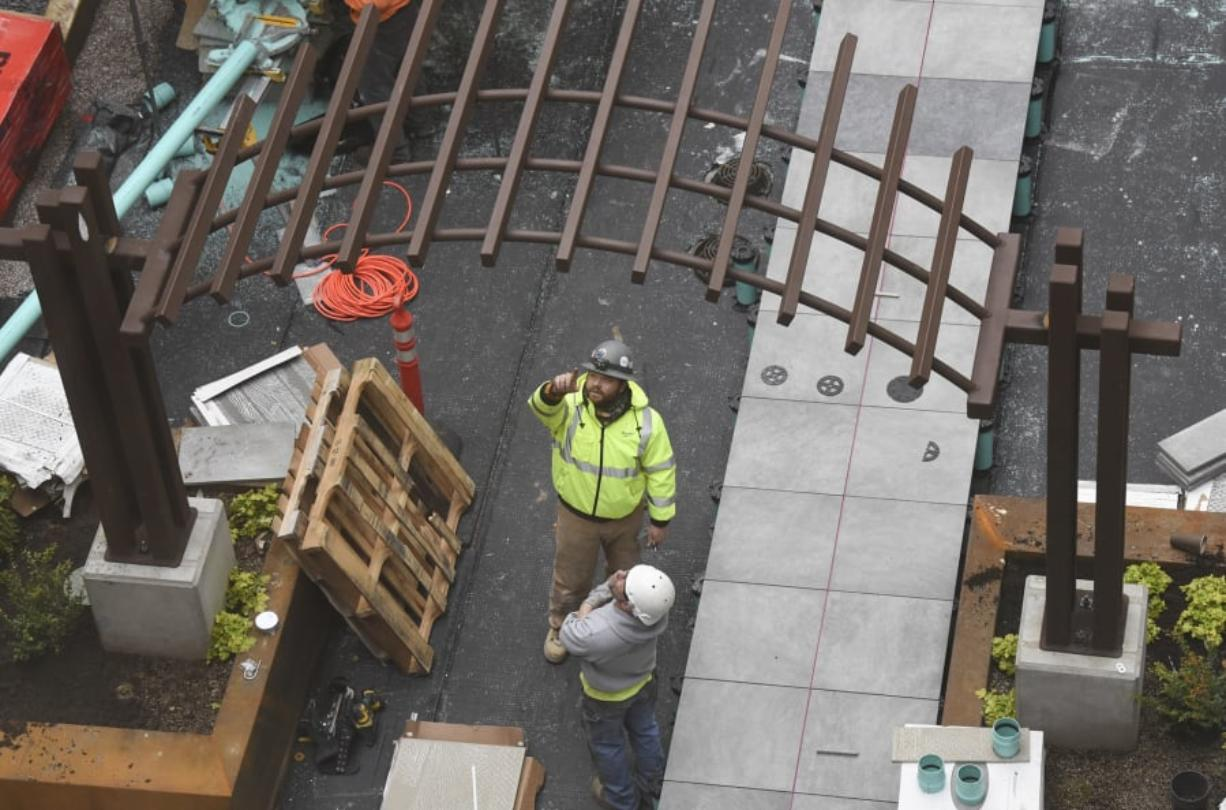 Workers look at a pergola in the courtyard at The Uptown Apartments in 2017.