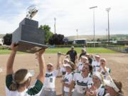 Woodland's Olivia Grey holds up the state championship trophy as her teammates celebrate after a 3-0 victory over W.F. West on Saturday, May 25, 2019 at Carlon Park in Selah, Wash.