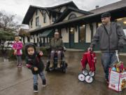 With a handful of gummy bears in one hand, Tobias reacts as the train pulls into the Vancouver rail station on its way to Seattle. Tobias, who was joined by his sister, Arianna Adams, 7, background from left, his mom, Jasmine Adams, and his dad, Matt Adams, was looking forward to taking his first train ride and going on his first vacation.