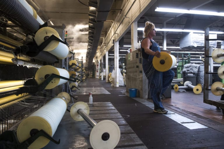 Jill Carroll carries a roll of wool from a carding machine at the Pendleton Washougal Mill. Nathan Howard/The Columbian