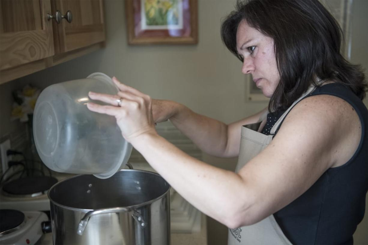 Gail Horn moves oils into a pot to make a new batch of soaps at her shop, The Soap Chest, in Camas on a recent Tuesday.