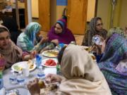 A group of women chat while eating iftar, the post-sunset meal during Ramadan, at the Islamic Society of Southwest Washington in Hazel Dell. Nighttime is also when practicing Muslims get their fill of water and other beverages.