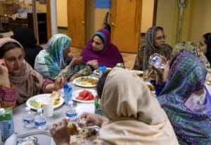 A group of women chat while eating iftar, the post-sunset meal during Ramadan, at the Islamic Societ