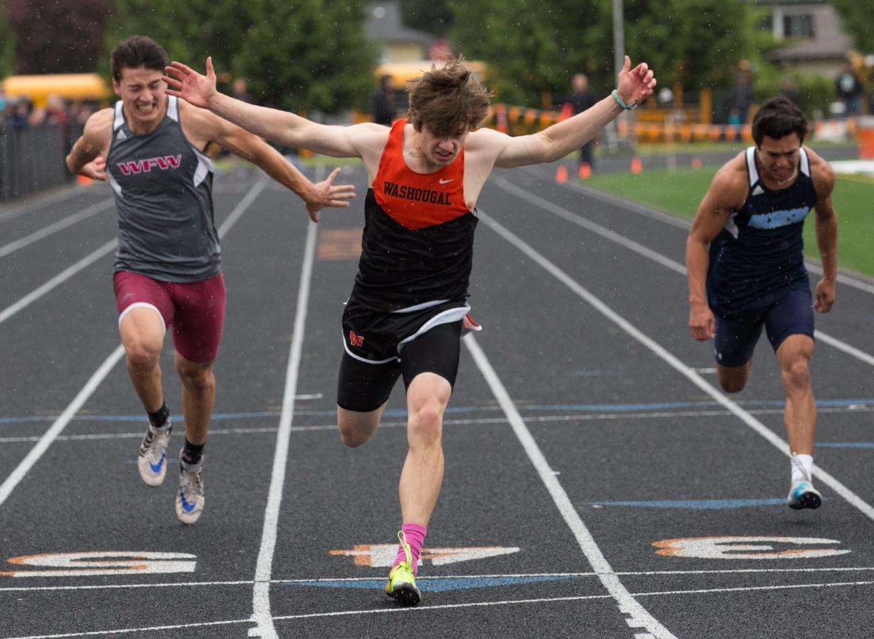 Washougal's Ryan Davy (center) stretches past the finish line as he wins the boys 100-meter run during the 2A District Track and Field Championships at Washougal High School, Friday, May 17, 2019.