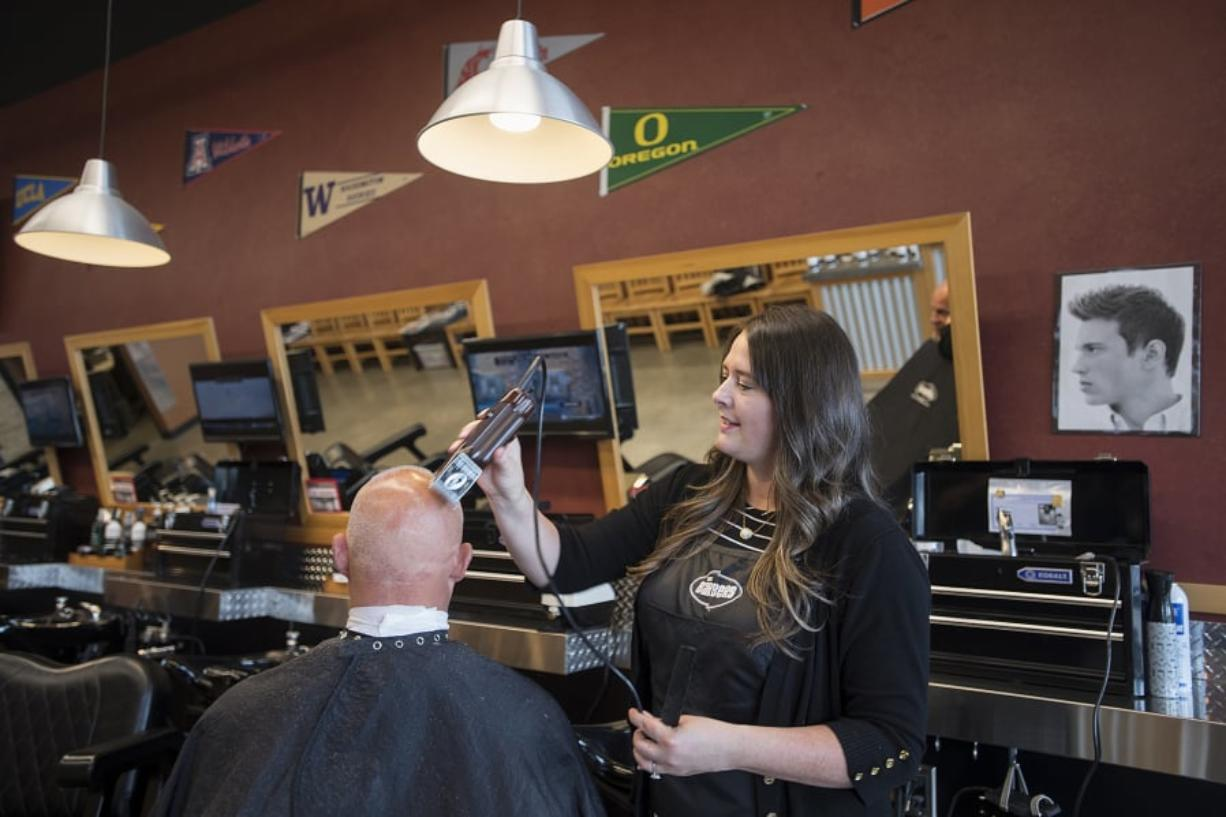 Camas resident Scott Binder stops by The Barbers to get a buzz cut and a neck shave from manager Tamie Brown. Photos by Amanda Cowan/The Columbian